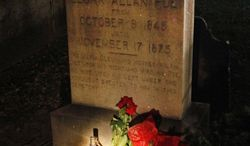 "A flashlight shines on items left on the gravestone of Edgar Allen Poe by people pretending to be the mysterious ""Poe Toaster"" in Baltimore early on Thursday, Jan. 19, 2012. (AP Photo/Patrick Semansky)"