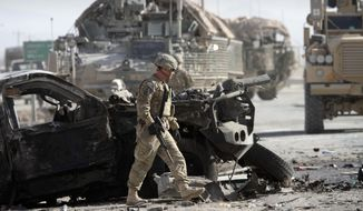 A U.S. soldier with the NATO led International Security Assistance Force (ISAF) walks Jan. 19, 2012, by a damaged vehicle at the scene of a suicide attack in Kandahar south of Kabul, Afghanistan. The attacker blew himself up at an entrance to a sprawling base for U.S. and NATO operations in southern Afghanistan, killing at least six civilians, police said. (Associated Press)