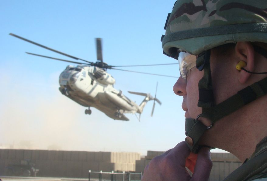 **FILE** A British military official with the NATO-led International Security Assistance Force (ISAF) adjusts his helmet Jan. 19, 2012, as a NATO helicopter lands at the Provincial Reconstruction Team compound in Lashkar Gah, Helmand province, south of Kabul, Afghanistan. (Associated Press)