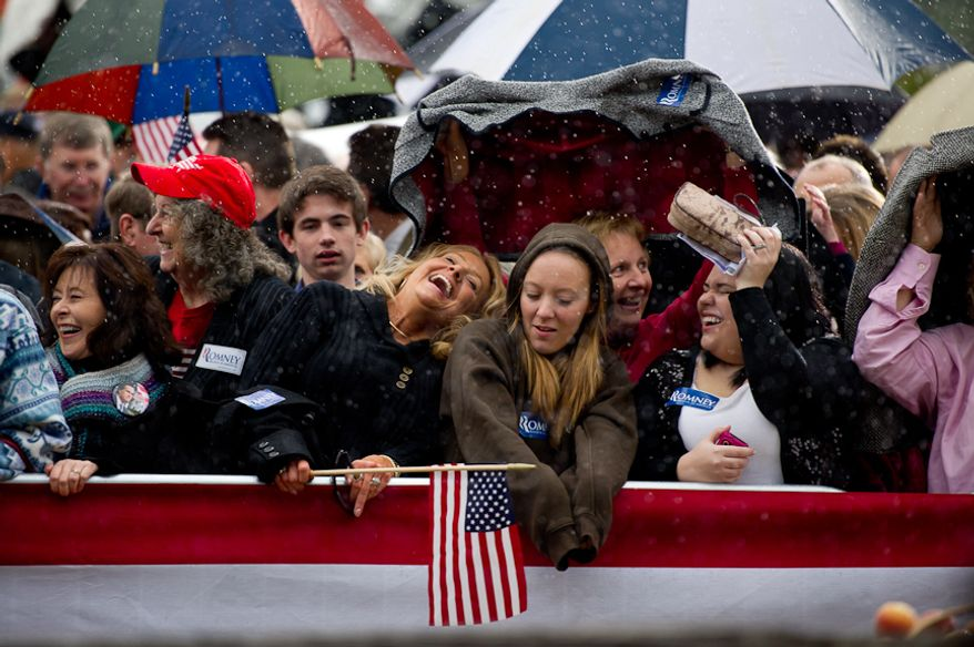 Supporters of Republican presidential candidate and former Massachusetts Gov. Mitt Romney try to shield themselves from the rain on Jan. 20, 2012, before Romney speaks at a rally at the Harmon Tree Farm in Gilbert, S.C. (Andrew Harnik/The Washington Times)