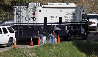 **FILE** Los Angeles Police investigators are seen Jan. 9, 2012, at a mobile command post as search operations for more human body parts near an end in Bronson Canyon in the Griffith Park area of Los Angeles. (Associated Press)