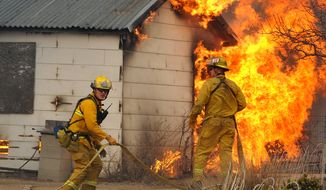 Firefighters wait for water Jan. 19, 2012, before attacking an outbuilding adjacent to a home in Pleasant Valley, Nev. Winds gusting up to 82 mph pushed a fast-moving brush fire south of Reno out of control as it burned several homes, threatened dozens more and forced more than 4,000 people to evacuate their neighborhoods. (Associated Press/The Reno Gazette-Journal)