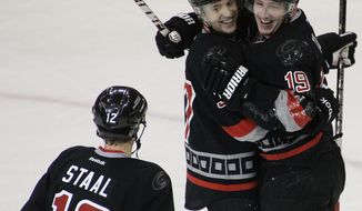 Carolina Hurricanes right wing Jiri Tlusty celebrates with teammates Tim Brent and Eric Staalafter scoring a goal against the Washington Capitals during the third period of an NHL hockey game in Raleigh, N.C., Friday, Jan. 20, 2012. The Hurricanes won 3-0. (AP Photo/Jim R. Bounds)
