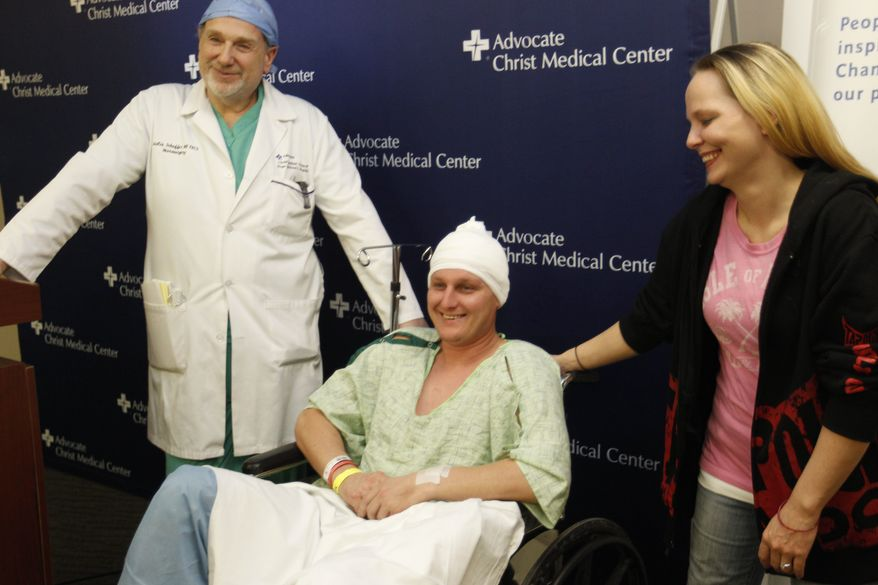 Neurosurgeon Leslie Schaffer, left, smiles with his patient Dante Autullo, and Dante's fiance, Gail Glaenzer, during a news conference at Advocate Christ Medical Center Friday, Jan. 20, 2012, in Oak Lawn, Ill. The trio spoke a day after Autullo underwent surgery to remove a 3 1/4-inch nail lodged in his brain after accidentally shooting himself with a nail gun. (AP Photo/M. Spencer Green)
