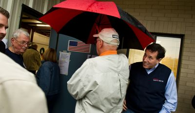 Republican presidential candidate Rick Santorum dodges the umbrella of Gary Robbins, of Chapin, S.C. as he goes to vote in the South Carolina Republican Primary at the Amicks Ferry Fire Station, Chapin, S.C., Saturday, Jan. 21, 2012. (Andrew Harnik/The Washington Times)