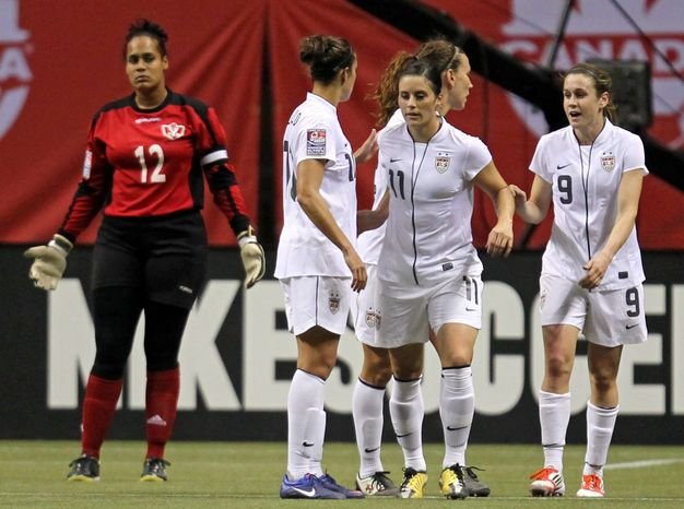 United States' Heather O'Reilly (9) celebrates her goal with teammates Ali Krieger (11) and Carli Lloyd (10) during the first half of a CONCACAF women's Olympic qualifying soccer match against Dominican Republic in Vancouver, British Columbia, Friday, Jan. 20, 2012. (AP Photo/The Canadian Press, Jonathan Hayward)