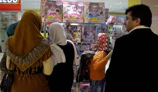 Iranians look at a doll display in a toy shop in Tehran on Friday. Police have closed down dozens of toy shops for selling Barbie dolls, part of a decades-long crackdown on signs of Western culture in Iran. (Associated Press)