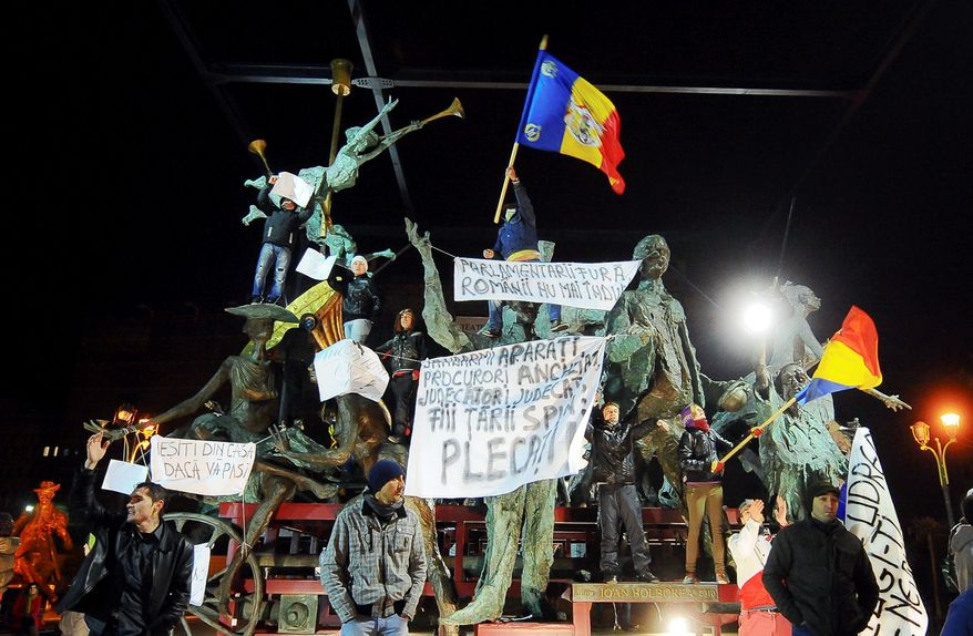 "Anti-government protesters holding banners that read ""Leave"" or ""Come out of your houses if you care"" climb on statues in front of a theater in downtown Bucharest, Romania, last Monday. They gathered as the prime minister warned that violent protests could jeopardize stability and economic growth. (Associated Press)"
