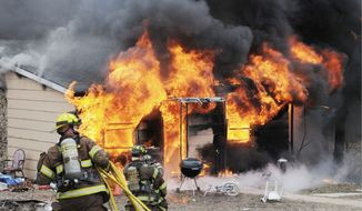 Firefighters battle a blaze from a shake-and-bake meth-lab explosion in 2010 at a house in Union, Mo. The crude new method of making methamphetamine, by combining raw and unstable ingredients in a 2-liter soda bottle, poses great risks. The concoction can explode, burning the user. (Associated Press)