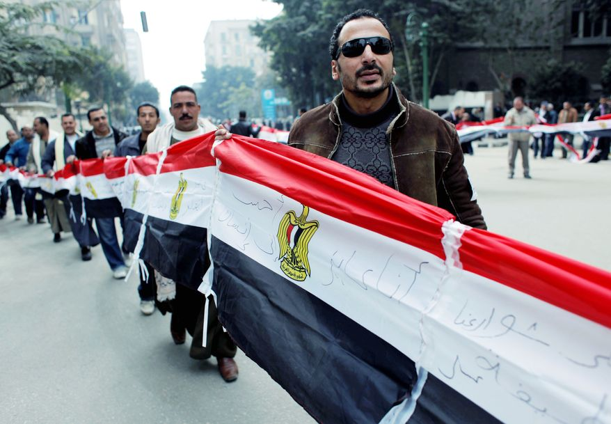 Egyptian protesters carry their national flag outside the People's Assembly building in Cairo during the assembly's opening session Monday. The newly elected assembly, which is made up overwhelmingly of Islamists, will elect a panel to draft a new constitution. Elections for the chamber were the first since Hosni Mubarak's ouster. (Associated Press)