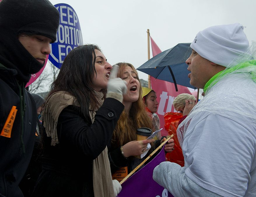 Pro-choice advocate Yasemin Ayarci of Levittown, Penn., left, challenges pro-life advocate Mike (who did not want to give his last name) of Rochester, N.Y., in front of the U.S. Supreme Court in Washington, D.C., on Monday, Jan. 23, 2012. (Barbara L. Salisbury/The Washington Times)