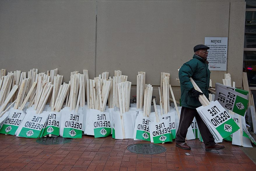 """George Hanna of the Knights of Columbus Supreme Council in New Haven, Conn., picks up """"Defend Life"""" signs to hand out as people exit Mass at Verizon Center in Washington. Advocates came from across the country for the annual March for Life. (Barbara L. Salisbury/The Washington Times)"""