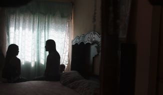 Karla Zepeda (left), 15, and Elisa Chavez, 22, sit Jan. 21, 2012, inside the home of Elisa's mother, in Zapopan, near Guadalajara, Mexico. Both claim that they agreed to lend their babies in a two-week photo shoot for $755 ($10,000 Mexican pesos) for an anti-abortion ad campaign but instead fell in an illegal adoption ring involving destitute young women trying to earn more for their children and childless Irish couples desperate to become parents. (Associated Press)