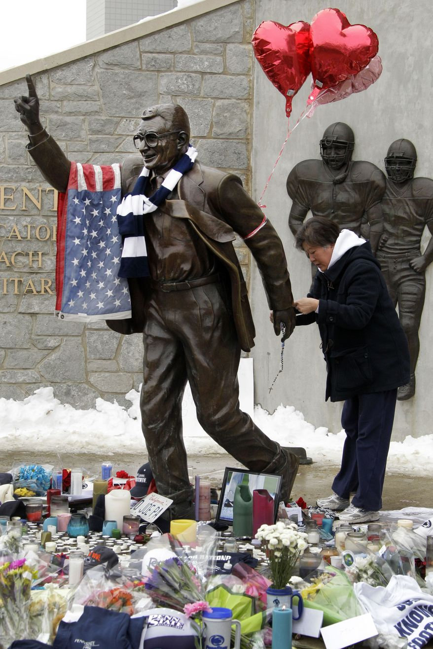 Penn State fan Maria Meyer attaches a set of rosary beads to a statue of Joe Paterno outside Beaver Stadium on the Penn State University campus after learning of his death on Sunday, Jan. 22, 2012, in State College,Pa. (AP Photo/Gene J. Puskar)