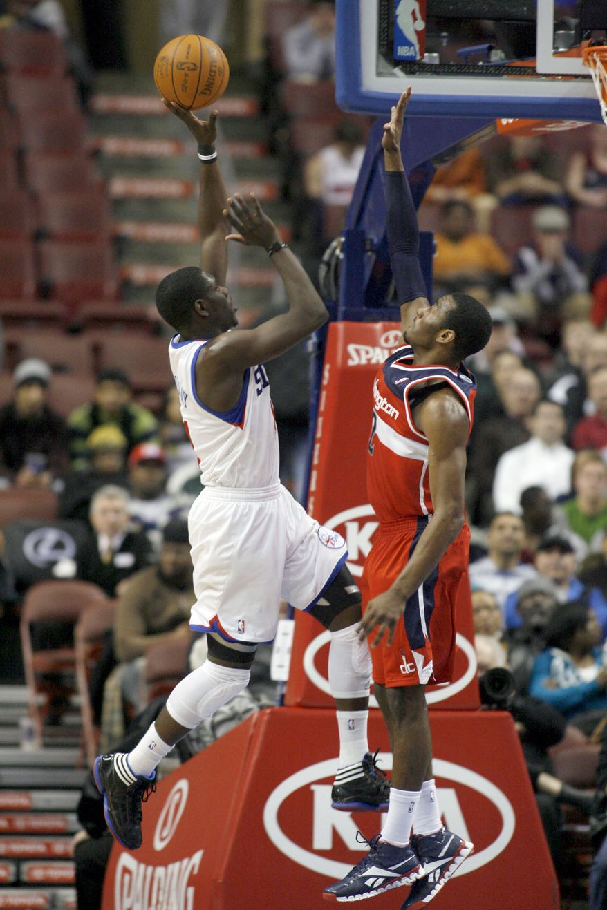 Philadelphia 76ers' Jure Holiday, left, scores against Washington Wizards' John Wall in the first half of an NBA game Monday, Jan, 23, 2012, in Philadelphia. The 76ers won 103-83. (AP Photo/H. Rumph Jr )