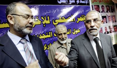 """""""Nobody can force me"""" to sit with Israelis, says Muslim Brotherhood leader Mahmoud Ezzat (left). He and Brotherhood leader Mohammed Badie appeared for a news conference last year in front of a banner that reads, """"Islam is the answer."""" (Associated Press)"""