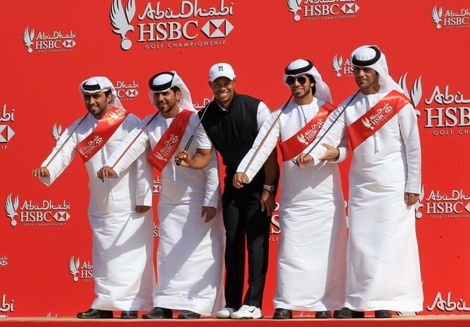 Tiger Woods moves with members of a traditional Emirati Ayala dance group in festivities leading up to the Abu Dhabi HSBC Golf Championship. (Associated Press)