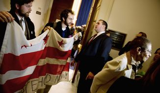 Occupy D.C. protesters Drew Veysey and Sam Jewler (from left) hold a D.C.  flag behind Delegate Eleanor Holmes Norton as she speaks to reporters following a hearing Tuesday about the occupation of McPherson Square.