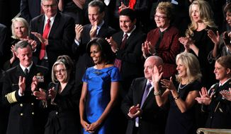 First lady Michelle Obama stands among several guests of the White House at the State of the Union address in this 2012 file photo. In the front row (from left) are Adm. William McRaven; Jackie Bray; Mrs. Obama; retired Navy Capt. Mark Kelly; Jill Biden, wife of the vice president; and Sgt. Ashleigh Berg. Two of the celebrity guests were Debbie Bosanek (second row with glasses), longtime secretary to billionaire Warren Buffett, and Laurene Powell Jobs (second row right with blond hair), widow of Apple co-founder Steve Jobs. (Associated Press) ** FILE **