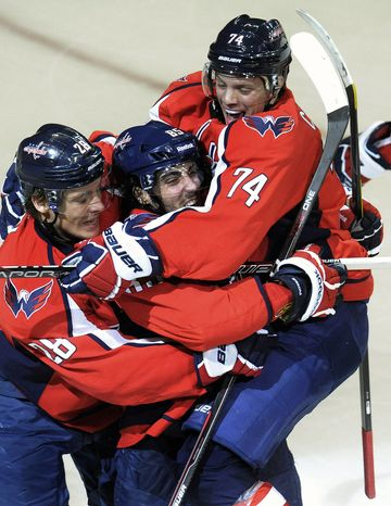 Washington Capitals' Mathieu Perreult, center, celebrates with Alexander Semin (28) and John Carlson (74) after scoring his third goal against the Boston Bruins during the third period of an NHL game, Tuesday, Jan. 24, 2012, in Washington. The Capitals won 5-3. (AP Photo/Richard Lipski)