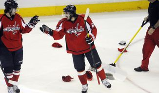 Washington Capitals' Mathieu Perreault, center, shakes hands with Marcus Johansson after completing a hat trick against the Boston Bruins during the third period of an hockey game, Tuesday, Jan. 24, 2012, in Washington. The Capitals won 5-3. (AP Photo/Richard Lipski)