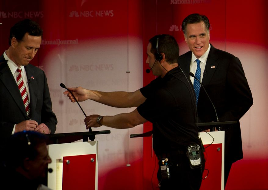 Republican presidential candidates (left to right): former Pennsylvania Senator Rick Santorum and former Massachusetts Governor Mitt Romney have their mics adjusted as they arrive on stage for The Republican Candidates Debate at the University of South Florida in Tampa, Fla., Monday, January 23, 2012. (Rod Lamkey Jr/ The Washington Times)