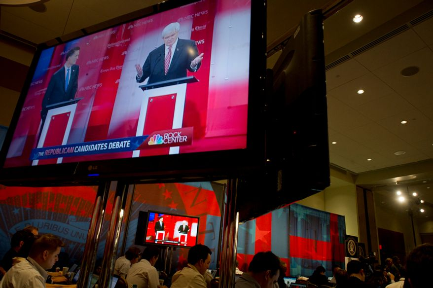 Republican presidential candidates former Massachusetts Governor Mitt Romney (left) and former House Speaker Newt Gingrich (right) are seen on the screens in the media filing center during the Republican Candidates Debate at the University of South Florida in Tampa, Fla., Monday, January 23, 2012. (Rod Lamkey Jr/ The Washington Times)
