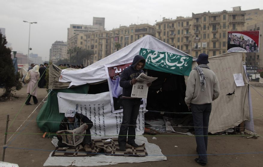 An Egyptian protester reads a newspaper outside a tent in Tahrir Square in Cairo on Tuesday, Jan. 24, 2012, a day before planned demonstrations to mark the first anniversary of the start of the uprising that deposed President Hosni Mubarak. (AP Photo/Muhammed Muheisen)
