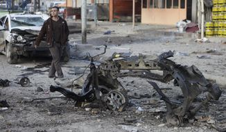 A man inspects the scene of a car bombing in the Sadr City neighborhood of eastern Baghdad on Tuesday, Jan. 24, 2012. (AP Photo/Karim Kadim)