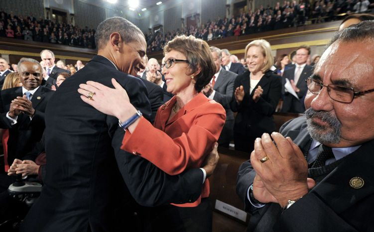 President Barack Obama embraces retiring Rep. Gabrielle Giffords, D-Ariz., as members of Congress applaud before his State of the Union address in front of a joint session of Congress Tuesday, Jan. 24, 2012, on Capitol Hill in Washington. (AP Photo/Saul Loeb)