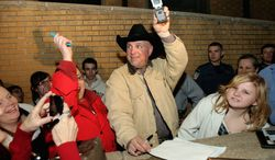 ASSOCIATED PRESS Garth Brooks holds up his cellphone for fans to call to his wife, Trisha Yearwood, Tuesday in Claremore, Okla., after he won a breach-of-contract suit against a Yukon, Okla., hospital that did not use money he donated for its declared purpose.