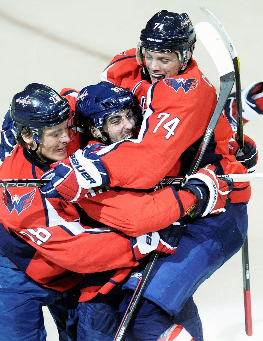 Washington Capitals' Mathieu Perreault (below, middle) did the damage with his stick Tuesday night as his hat trick helped beat the Stanley Cup-champion Boston Bruins 5-3. (AP Photo/Richard Lipski)