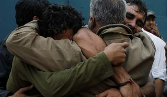 Family members mourn the deaths of three men in Karachi, Pakistan, on Wednesday. Three lawyers were gunned down and one was injured in an ambush by unidentified gunmen riding on a motorcycle, police said. The dead included a father, son and nephew. The motive is not yet known. (Associated Press)