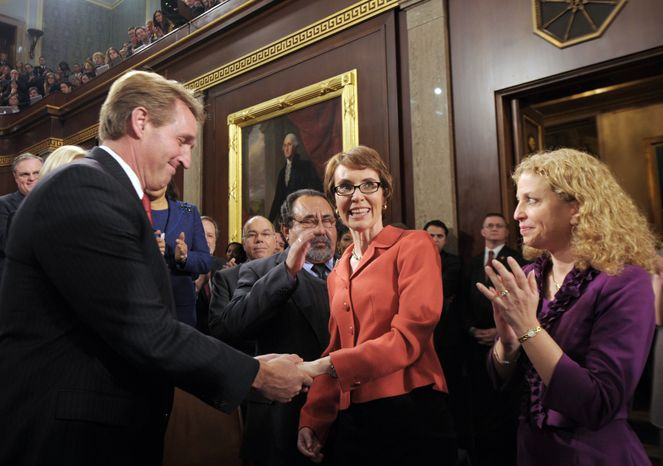 Rep. Gabrielle Giffords (center), Arizona Democrat, is greeted by Rep. Jeff Flake, Arizona Republican, and Rep. Debbie Wasserman Schultz, Florida Democrat, before President Obama's State of the Union address to Congress on Tuesday, Jan. 24, 2012, on Capitol Hill in Washington. (AP Photo/Saul Loeb, Pool)