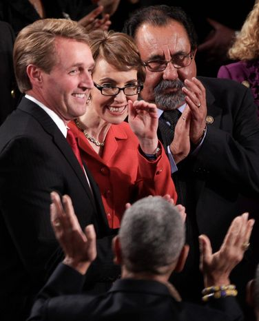 Rep. Gabrielle Giffords, a moderate Democrat, takes her place between Rep. Jeff Flake, a conservative Republican, and Rep. Raul M. Grijalva, a liberal Democrat. Colleagues started a tribute last year by sitting with members of the other party. (Associated Press)