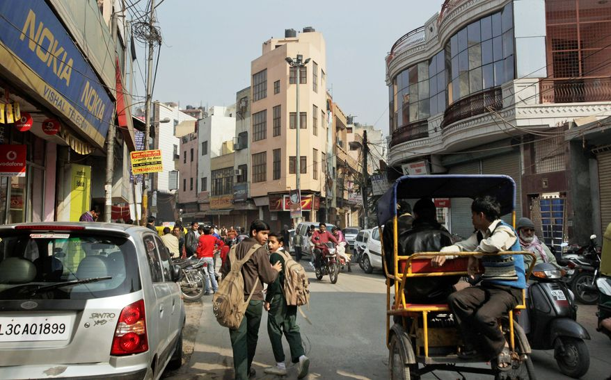 In this Dec. 20, 2011 photo, commuters move past congested houses built close to each other in India's most crowded northeast district of New Delhi, India. If a major earthquake were to strike India's seismically vulnerable capital, this neighborhood, home to 2.2 million people and India's most crowded district, would likely collapse into an apocalyptic nightmare. (AP Photo/Manish Swarup)