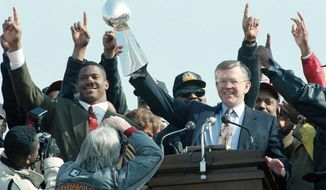 Redskins coach Joe Gibbs, surrounded by players, hoists the franchise's third Vince Lombardi Trophy. (Associated Press)