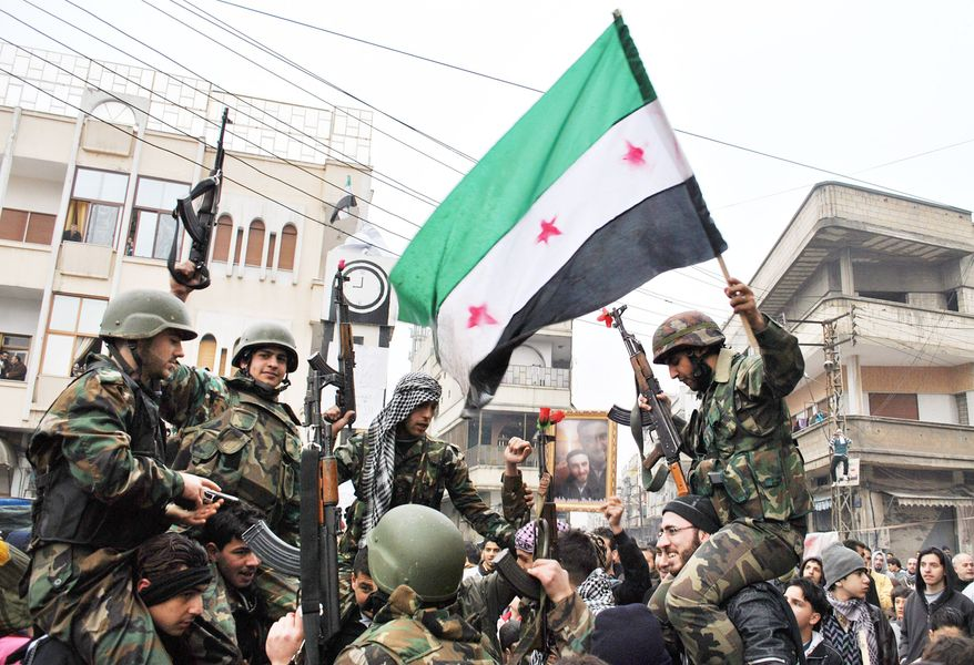 """Syrian army defectors celebrate with the Syrian revolution flag shortly after they joined the anti-regime protesters in Homs province on Thursday, the same day Syrian troops stormed a suburb of Damascus as the 10-month uprising inches ever closer to the capital. """"A fierce battle is taking place, and troops are shelling areas with heavy machine gunfire,"""" an activist said. (Associated Press)"""