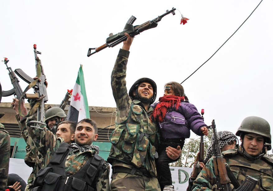With a child on his hip and a rifle in his hand, a Syrian army defector celebrates with comrades after they joined the anti-regime forces in Homs province. The Syrian government crackdown has killed more than 5,400 people since March.