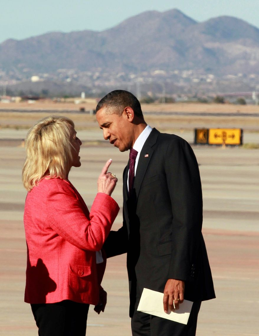 Arizona Gov. Jan Brewer makes a point to President Obama upon his arrival Wednesday at Phoenix-Mesa Gateway Airport. Mrs. Brewer said he took issue with a passage in her book that described an encounter in an unflattering manner. (Associated Press)
