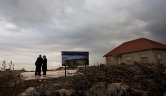 In this photo taken Monday, Jan. 23, 2012, Jewish settlers walk near the remaining foundations of a demolished house, with a sign wishing its rebuilding, in the unauthorized West Bank Jewish settlement of Migron. (AP Photo/Sebastian Scheiner)