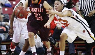 Virginia Tech guard Monet Tellier drives past Maryland's Kim Rodgers, right, and Laurin Mincy in the second half  in College Park, Md., Thursday, Jan. 26, 2012. Tellier contributed a game-high 31 points to Virginia Tech's 75-69 win. (AP Photo/Patrick Semansky)
