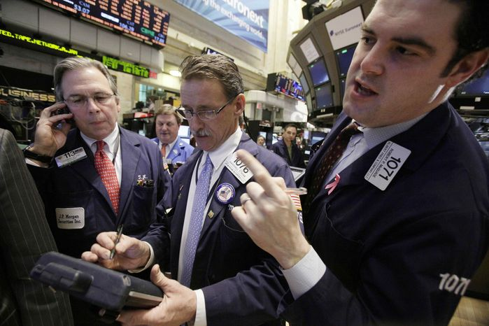 In this Jan. 25, 2012, photo, traders Thomas Kay, left, Marshall Ryan, center, and Robert McQuade work on the floor of the New York Stock Exchange. World stock markets rose on Thursday, Jan. 26, after the U.S. Federal Reserve pledged to keep intere