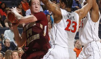 Boston College center Dennis Clifford looks for room around Virginia forward Mike Scott (23) and Virginia forward Akil Mitchell (25) during the first half Thursday, Jan. 26, 2012, in Charlottesville, Va. (AP Photo/Andrew Shurtleff)