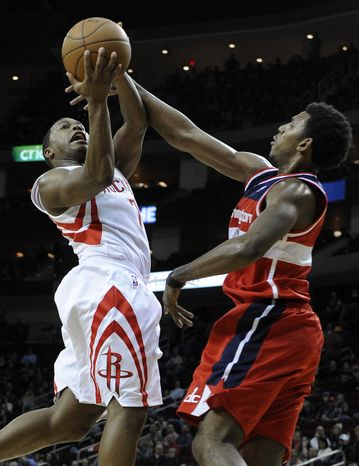 Houston Rockets' Kyle Lowry goes to the basket against Washington Wizards' Nick Young in the second half Friday, Jan. 27, 2012, in Houston. (AP Photo/Pat Sullivan)