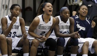 Georgetown forward Brittany Horne, left, forward Tia Magee (2) and others cheer their teammates in a game against Syracuse in Washington, Sunday, Jan. 15, 2012. Georgetown beat Syracuse 69-42. (AP Photo/Ann Heisenfelt)