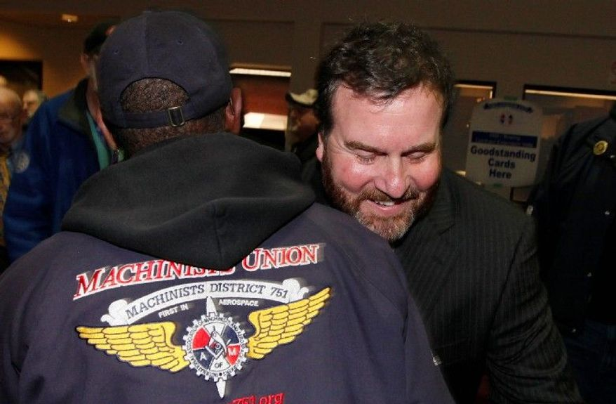 Mark Blondin, Machinists Union national aerospace coordinator, hugs a Boeing worker after the announcement Dec. 7 that the union voted for a new contract. A Republican bill would require workers to reaffirm their faith in unions with a new vote every three years. (Associated Press)