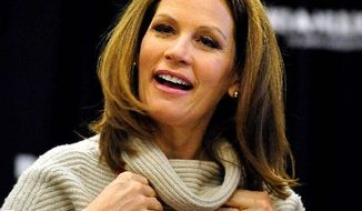 FILE - In this Dec. 3, 2011, file photo Republican presidential candidate Rep. Michele Bachmann, R-Minn., expresses appreciation as she puts on a gift from a supporter during the book-signing event in Aiken, S.C. Bachmann told The Associated Press Wednesday, Jan. 25, 2012, that she'll seek a 4th term in Congress following her failed presidential bid. (AP Photo/Rainier Ehrhardt, File)