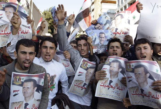 Protesters shout slogans as they carry pictures of Syrian President Bashar Assad and Syrian flags during a demonstration in front of the Russian Embassy in Beirut on Sunday, Jan. 29, 2012, to express gratitude for Russia's support of Syria. (AP Photo/Bilal Hussein)