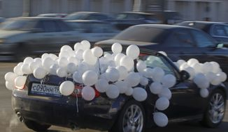 A car decorated with white balloons is one of hundreds driving around Moscow's Garden Ring road during a protest against Russian President Vladimir Putin in Moscow on Sunday, Jan. 29, 2012. (AP Photo/Mikhail Metzel)